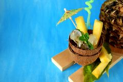 Ingredients for pina colada cocktail. Ice cubes and pineapple pieces served in a coconut half decorated with an umbrella. On blue background Stock Images