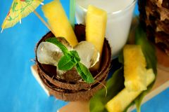 Ingredients for pina colada cocktail. Ice cubes and pineapple pieces served in a coconut half decorated with an umbrella. On blue background Stock Photography