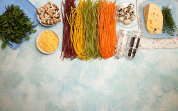 Ingredients for preparation dinner. Overhead of pasta tagliatel. Le of different colors, quail eggs, gouda cheese, honey mushrooms on white blue background Stock Photo