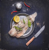 Ingredients for preparation of raw cod with herbs and lemon in a frying pan on wooden rustic background top view close up Royalty Free Stock Photography