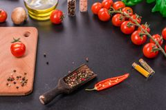 Ingredients for preparation of tasty Italian pizza. Cherry tomato, spices, basil, chili pepper stock photo
