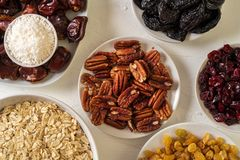 Ingredients for preparing Healthy organic energy balls- dates, dried apricot, oat flakes, raisin, dried cranberries, pecan nuts,. Coconut shavings on white royalty free stock photography