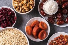 Ingredients for preparing Healthy organic energy balls- dates, dried apricot, oat flakes, raisin, dried cranberries, pecan nuts,. Coconut shavings on gray stock photo