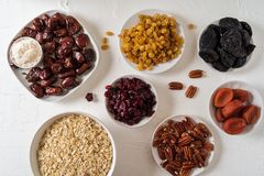 Ingredients for preparing Healthy organic energy balls- dates, dried apricot, oat flakes, raisin, dried cranberries, pecan nuts,. Coconut shavings on white stock photo