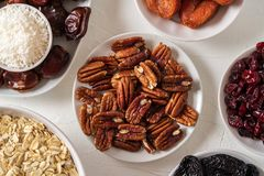 Ingredients for preparing Healthy organic energy balls- dates, dried apricot, oat flakes, raisin, dried cranberries, pecan nuts,. Coconut shavings on white stock images