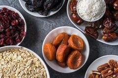 Ingredients for preparing Healthy organic energy balls- dates, dried apricot, oat flakes, raisin, dried cranberries, pecan nuts,. Coconut shavings on gray stock photography
