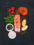 Ingredients. Raw salmon filet, lemon, cherry and heirloom tomatoes, fresh mint, spices on rustic wooden board over dark Royalty Free Stock Images