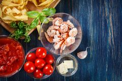 Ingredients ready for preparing pappardelle pasta with shrimp, t. Omatoes and herbs. Italian cuisine. Top view Stock Image