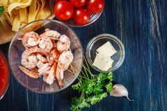 Ingredients ready for preparing pappardelle pasta with shrimp, t. Omatoes and herbs. Italian cuisine. Top view Royalty Free Stock Images