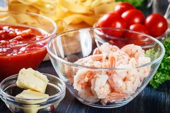 Ingredients ready for preparing pappardelle pasta with shrimp, tomatoes and herbs. Italian cuisine Stock Image