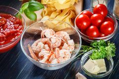 Ingredients ready for preparing pappardelle pasta with shrimp, tomatoes and herbs. Italian cuisine Royalty Free Stock Photography