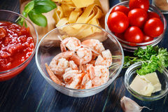 Ingredients ready for preparing pappardelle pasta with shrimp, tomatoes and herbs Stock Images