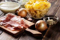 Ingredients ready for preparing pappardelle with prosciutto and cheese sauce Stock Photos