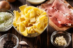 Ingredients ready for preparing pappardelle with prosciutto and cheese sauce. Food and drink Royalty Free Stock Images