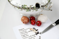 Ingredients and recipe for making soup. Soup tureen with spoon, onion, tomatoes, garlic, peppercorns, a knife and a recipe for making soup Royalty Free Stock Image
