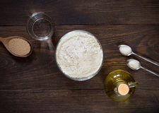 Ingredients for recipe pizza dough on dark wooden background. Royalty Free Stock Images