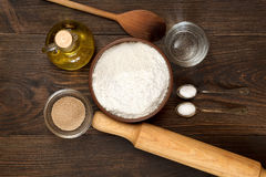 Ingredients for recipe pizza dough on dark wooden background. Royalty Free Stock Photos