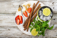 Ingredients for refreshing summer healthy vitamin drinks: lime, mint, berries, fruit, ice, brown sugar, cinnamon sticks. On white round cutting Board for filing Stock Photography