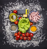 Ingredients for risotto with ham, vegetables and spices on wooden rustic background top view close up stock image