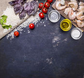 Ingredients for risotto with prawns, vegetables, spices, white wine border, place for text wooden rustic background top view stock image
