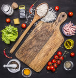 Ingredients for risotto, rice, salt, pepper, tomatoes, ham, butter, cheese and grater on wooden rustic background top view close u Stock Photos