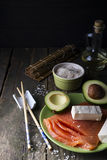 Ingredients for rolls philadelphia. Traditional asian ingredients Fresh salmon steak filet, uncooked rice, avocado, sheese on old wooden background Stock Photo