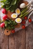 Ingredients for the salad: egg, sorrel, tomato, radish. Vertical top view Royalty Free Stock Photo