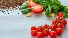 Ingredients for salad: raw cherry tomatoes, basil, garlic, pepper on the gray table with copy space. Cooking concept. Italian food. Ingredients for salad: raw Royalty Free Stock Images