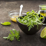Ingredients for salad: rucola, root salad, olive oil, limes on a dark background. Seasonal Healthy Eating. Ingredients for salad: rucola, root salad, olive oil Stock Images