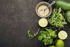 Ingredients for salad: rucola, root salad, olive oil, limes on a dark background. Seasonal Healthy Eating. Ingredients for salad: rucola, root salad, olive oil Stock Photos