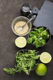 Ingredients for salad: rucola, root salad, olive oil, limes on a dark background. Seasonal Healthy Eating. Ingredients for salad: rucola, root salad, olive oil Royalty Free Stock Images