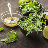 Ingredients for salad: rucola, root salad, olive oil, limes on a dark background. Seasonal Healthy Eating. Ingredients for salad: rucola, root salad, olive oil Royalty Free Stock Image
