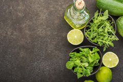 Ingredients for salad: rucola, root salad, olive oil, limes on a dark background. Seasonal Healthy Eating. Ingredients for salad: rucola, root salad, olive oil Stock Image