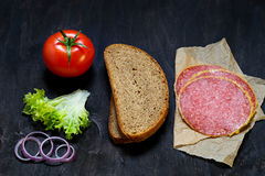 Ingredients for sandwich: bread, tomato, salami, salad, onion Stock Images