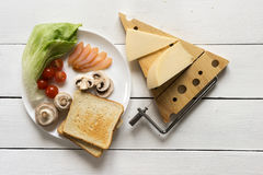 Ingredients for a sandwich on a white plate for breakfast or lun. Ingredients for a sandwich of toasted toasts with cheese, mushrooms, salad, cherry and ham on a Stock Photography