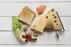 Ingredients for a sandwich on a white table for breakfast or lun. Ingredients for a sandwich of toasted toasts with cheese, mushrooms, salad, cherry and ham on a Royalty Free Stock Images