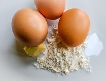 Free range eggs seen with flour and butter for making a cake. Royalty Free Stock Photos