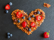 Ingredients in shape of heart to cook a breakfast. Blueberries, strawberries and granola made from oat flakes, dried fruits, nuts Stock Photography