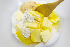 Ingredients for shortcrust pastry as flour, eggs, butter and sug. Ar with a stirring spoon in a bowl, baking background, view from above, selected focus, narrow Stock Photography