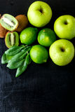 Ingredients for smoothie. Green fruits on black wooden background. Apple, lime, spinach, kiwi. Detox. Healthy food. Top view. Copy Stock Image