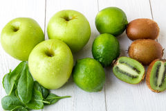 Ingredients for smoothie. Green fruits on white wooden background. Apple, lime, spinach, kiwi. Detox. Healthy food. Ingredients for smoothie. Green fruits on royalty free stock photos