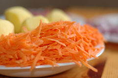 Ingredients for soup. Grated carrots and potatoes on a white plate Stock Images