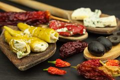 Ingredients for spicy barbecue on the wooden spoon. Dried chillies and spicy peppers filled with cheese. Stock Images
