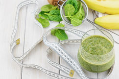The Ingredients spinach, buttermilk, kiwi and banana for a tasty smoothie and a centimeter to measure the results of a diet. Stock Photography
