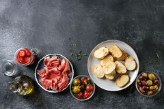 Ingredients for tapas. Ingredients for making tapas or bruschetta. Crusty bread, ham prosciutto, sun dried tomatoes, olive oil, olives, pepper, greens on plates Royalty Free Stock Images