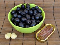 Ingredients for tapenade: stoned black olives in a green bowl, anchovy fillets in a yellow oval tin can and two big cloves of garl stock image