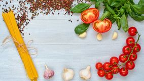 Ingredients for tasty pasta: raw cherry tomatoes, basil, garlic, pepper on the gray concrete kitchen table. Cooking concept. Italian food. Top view with space Royalty Free Stock Photography