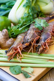 Ingredients for Thai tom yam soup. Laid out on a kitchen counter with tiger prawns, mushrooms, ginger, lemongrass, limes, celery, parsley and spices Stock Images