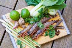 Ingredients for Thai tom yam soup. Laid out on a kitchen counter with tiger prawns, mushrooms, ginger, lemongrass, limes, celery, parsley and spices Royalty Free Stock Images