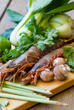 Ingredients for Thai tom yam soup. Laid out on a kitchen counter with tiger prawns, mushrooms, ginger, lemongrass, limes, celery, parsley and spices Royalty Free Stock Photography
